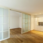 Portes corredisses blanques amb vidre lacobel blanc parquet roure 3 lames natural